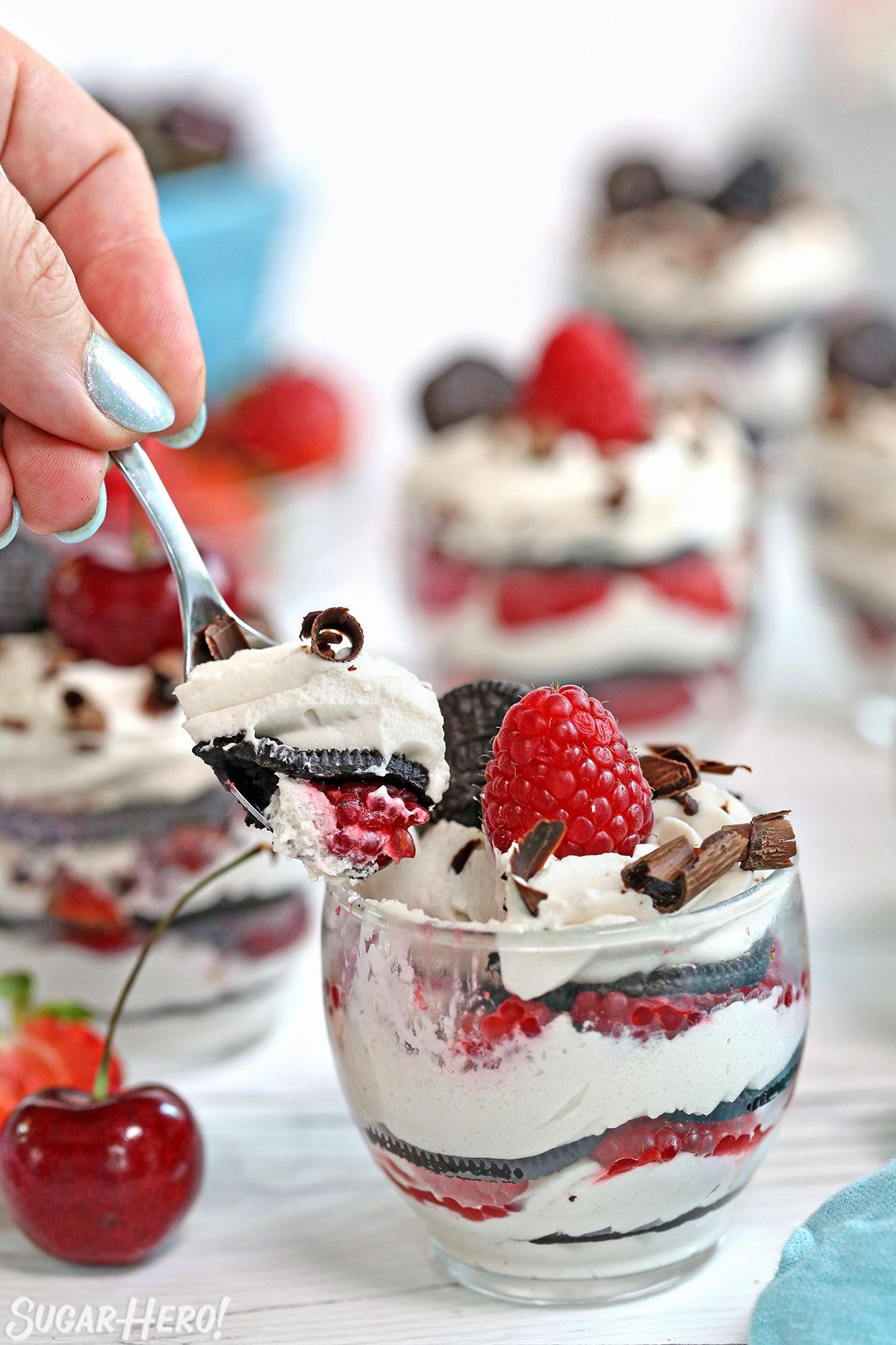 Mini Oreo Icebox Cakes - taking a spoonful of no-bake Oreo cake | From SugarHero.com