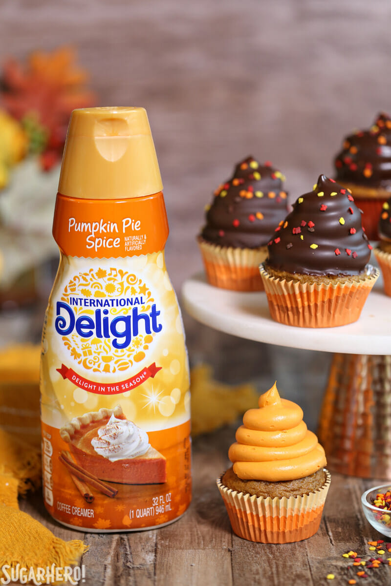 Pumpkin Spice Hi-Hat Cupcakes - Straight shot of creamer and cupcakes displayed on a stand. | From SugarHero.com