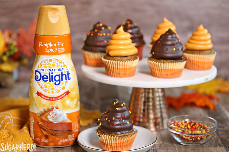 Pumpkin Spice Hi-Hat Cupcakes - A straight shot of the cupcakes displayed on a cake stand. | From SugarHero.com