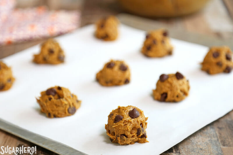 3-Ingredient Pumpkin Chocolate Chip Cookies - scooping the pumpkin chocolate chip cookie dough out onto a baking sheet | From SugarHero.com
