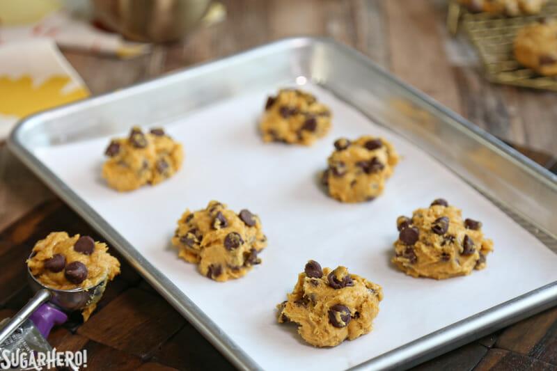 Pumpkin Chocolate Chip Cookies - scoops of pumpkin chocolate chip cookie dough on a baking sheet   From SugarHero.com