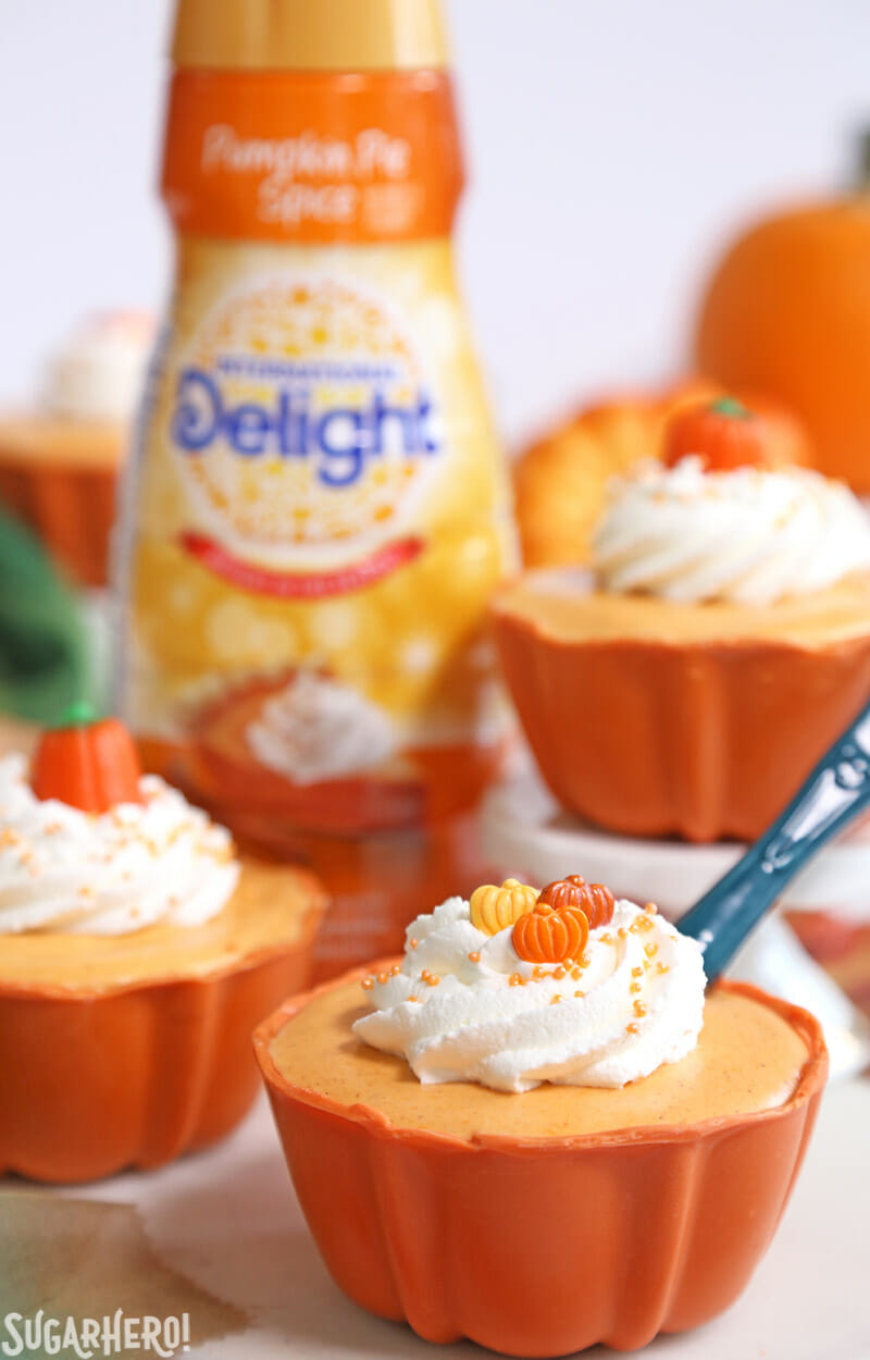 Pumpkin Spice Mousse Cups - mousse cup with spoon sticking out of it and pumpkin spice creamer bottle in background | From SugarHero.com
