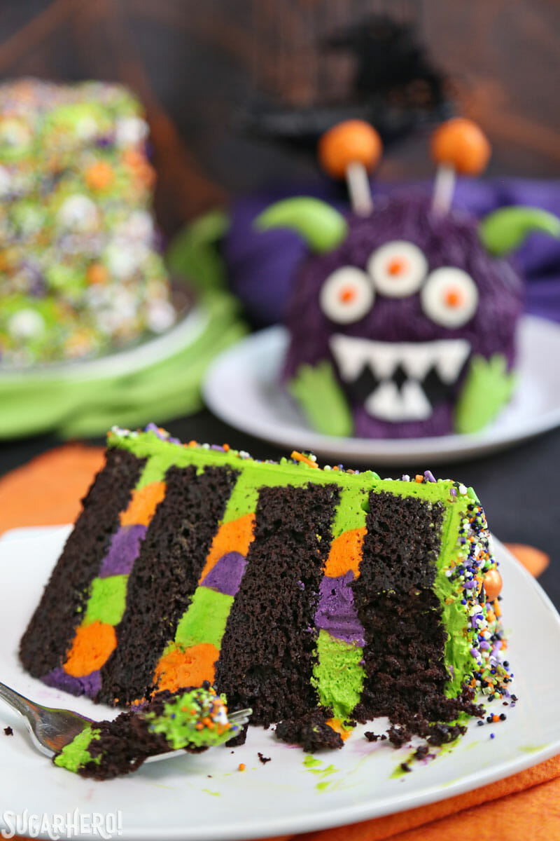 Monster Cake - slice of cake with a bite taken out of it and monster cake in the background | From SugarHero.com