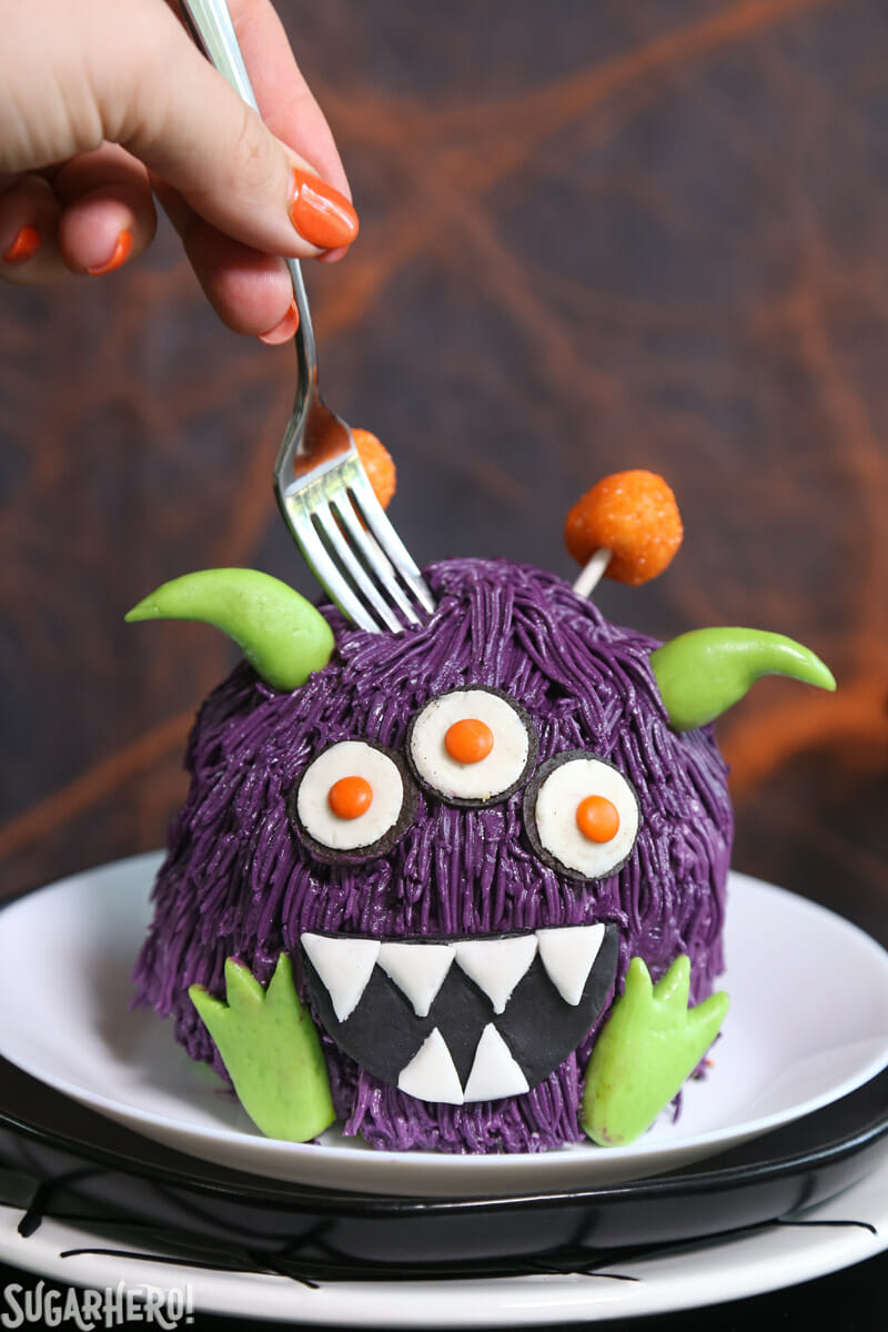 Monster Cake - mini monster cake on a plate with a fork digging into the top of the cake | From SugarHero.com