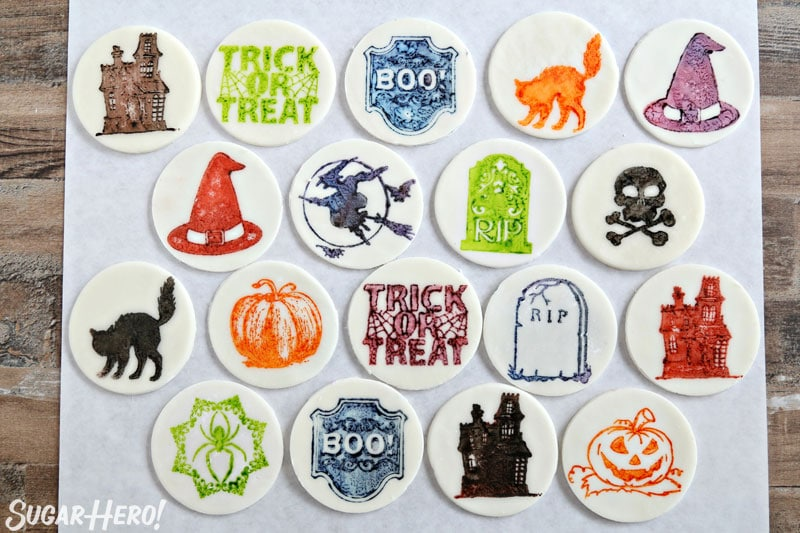 Stamped Halloween Cupcakes - group of fondant circles stamped with different Halloween designs and colors | From SugarHero.com
