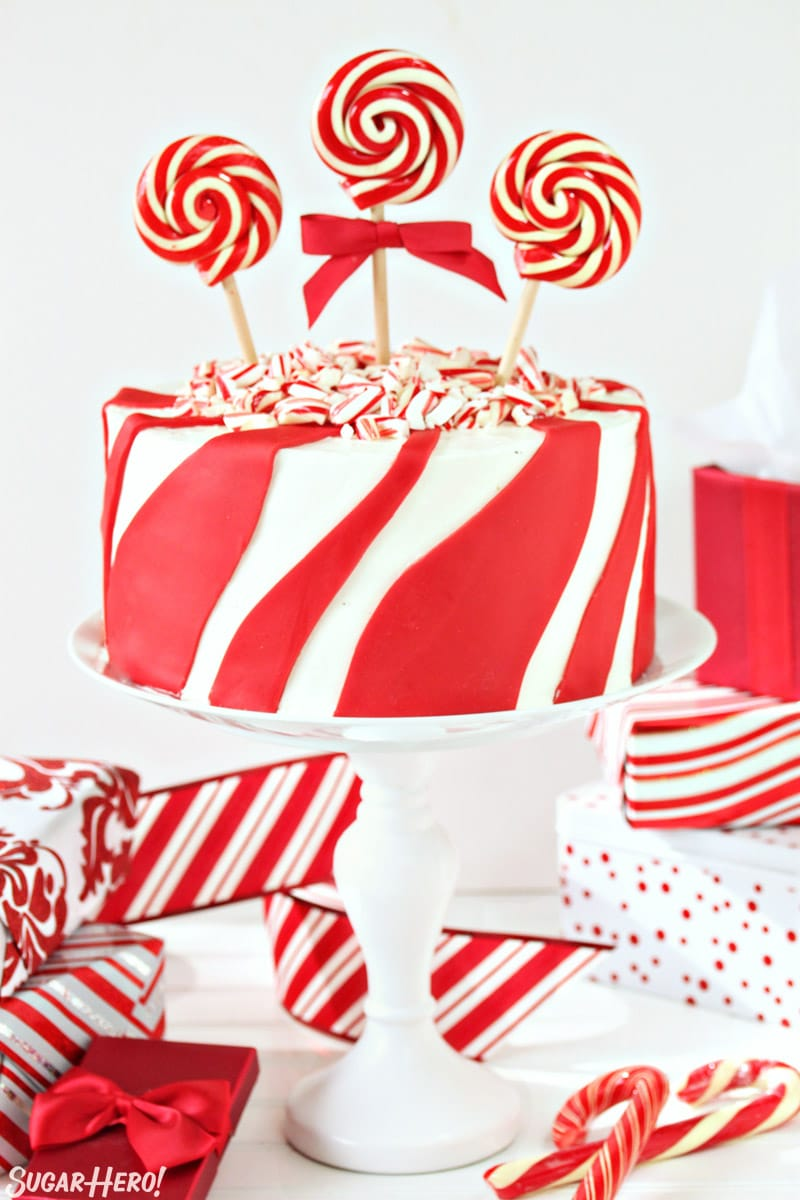 Candy Cane Chocolate Cake - vertical image of cake on cake stand with wrapped presents around | From SugarHero.com