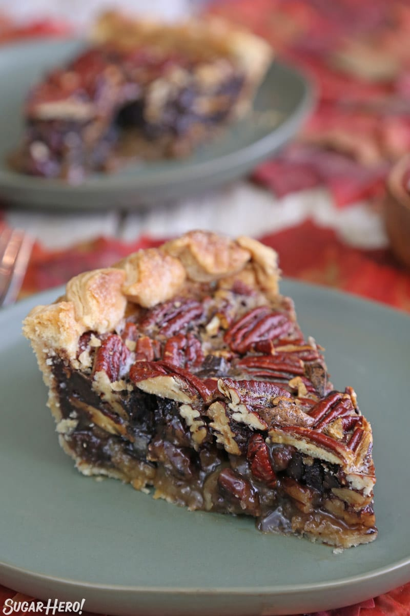 Deep Dish Pecan Pie - slice of deep dish pie on a green plate with another slice in the background | From SugarHero.com