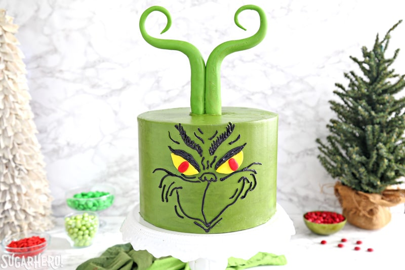 Grinch Cake - green cake with a Grinch face piped in black buttercream, and green Grinch fondant hair | From SugarHero.com
