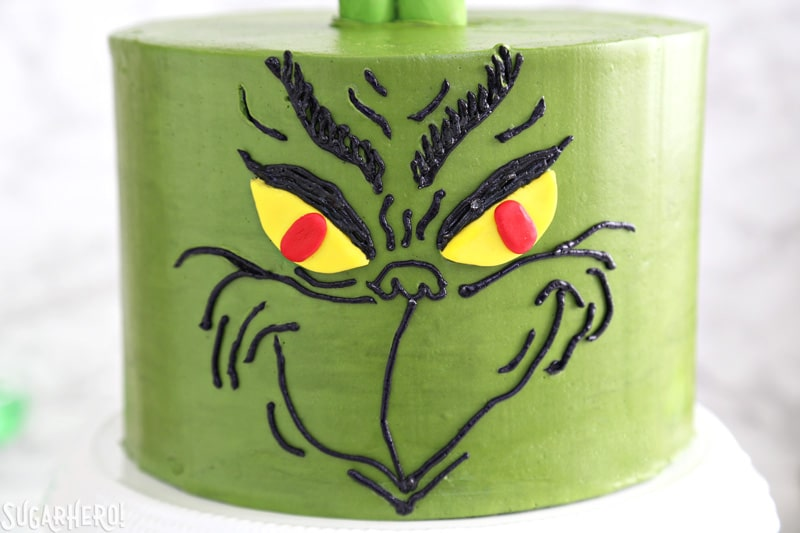 Grinch Cake - close-up of the Grinch's face, done in black buttercream on a green cake | From SugarHero.com