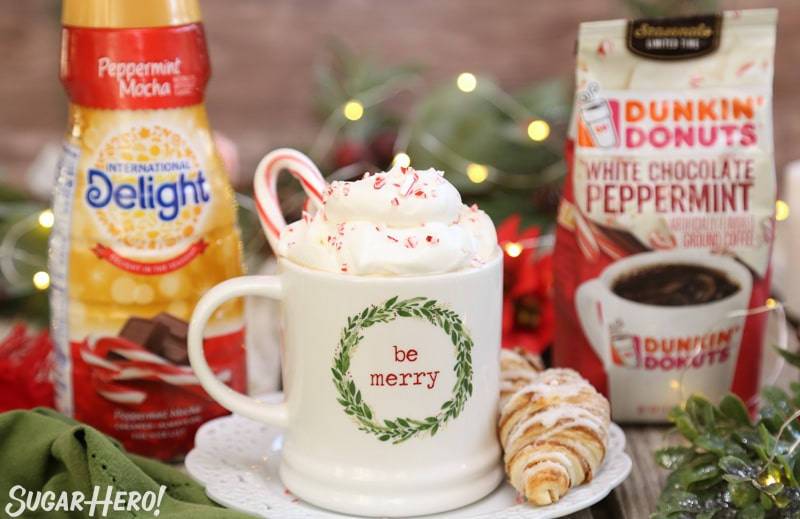 Peppermint Affogato - cup of coffee with whipped cream and candy cane pieces, surrounded by a coffee and creamer package | From SugarHero.com