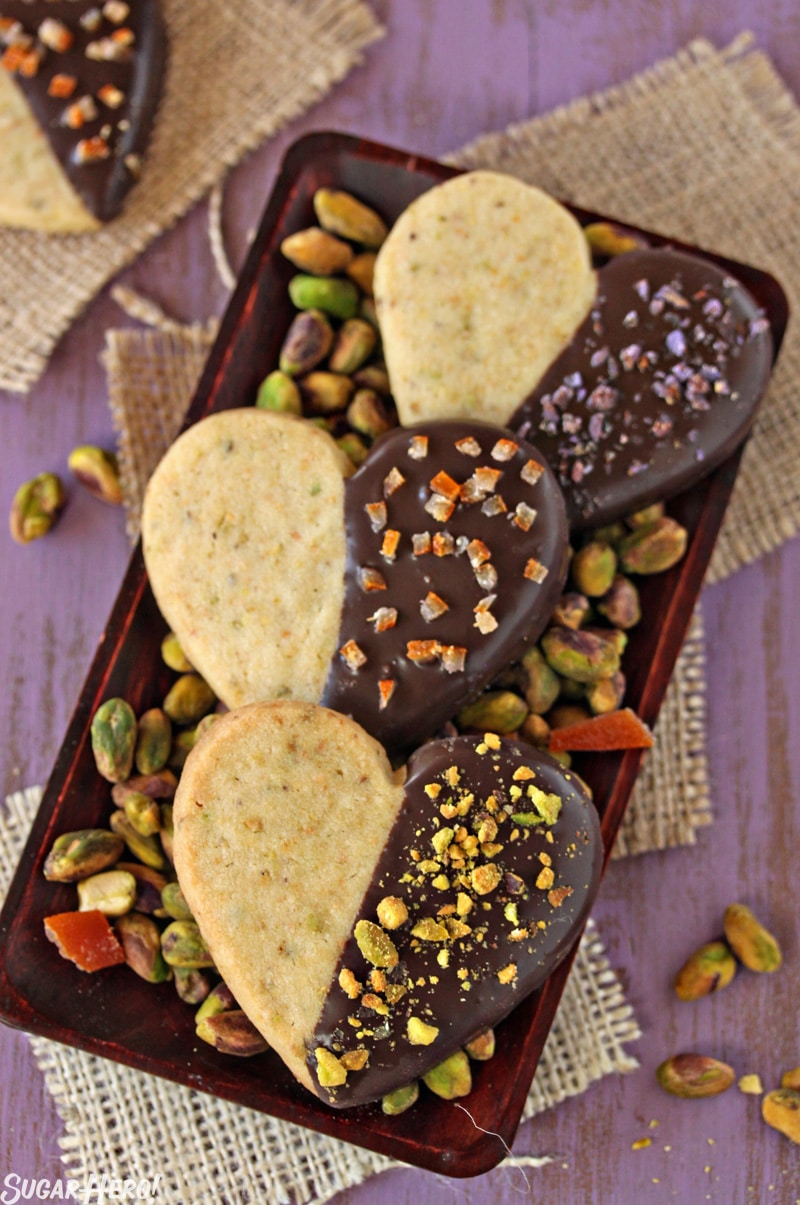 Pistachio Shortbread Cookies - Three cookies displayed on a tray with pistachios. | From SugarHero.com