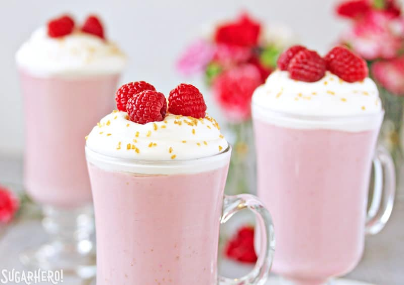 Raspberry White Hot Chocolate - Three separate glasses of hot chocolate and raspberries on top | From SugarHero.com