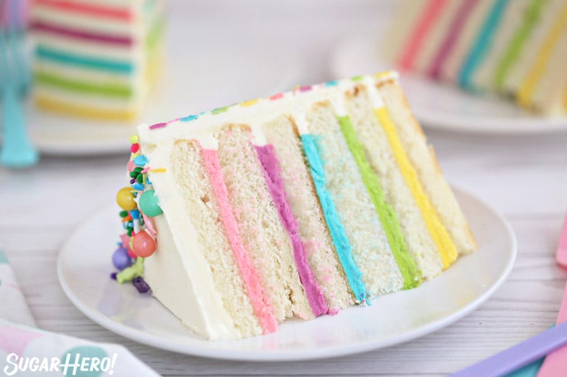 Striped Buttercream Balloon Cake - close-up picture of a single slice of cake, with several slices in the background   From SugarHero.com