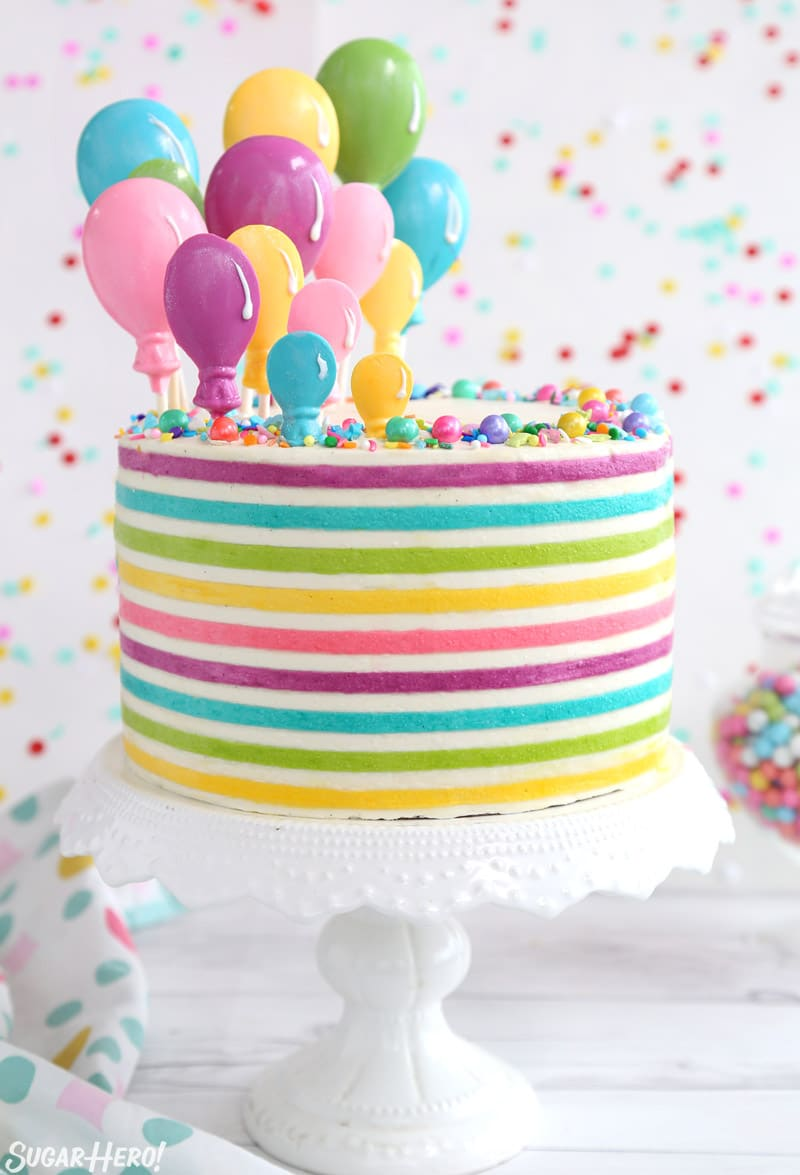 Striped Buttercream Balloon Cake - a round cake with bright, colorful buttercream stripes and candy balloons rising from the top | From SugarHero.com