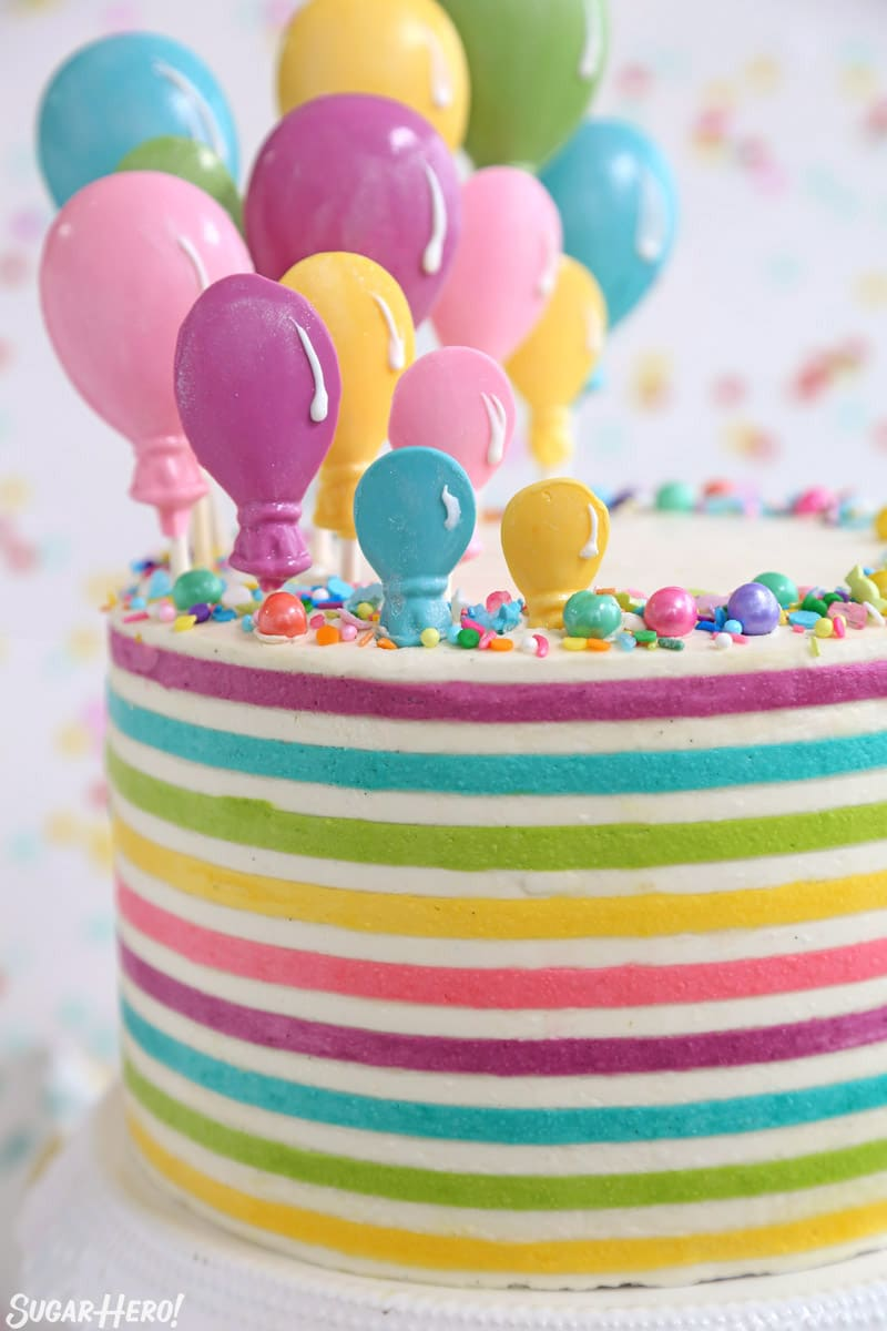 Striped Buttercream Balloon Cake - close-up vertical picture of colorful buttercream stripes and candy balloons on top of the cake | From SugarHero.com