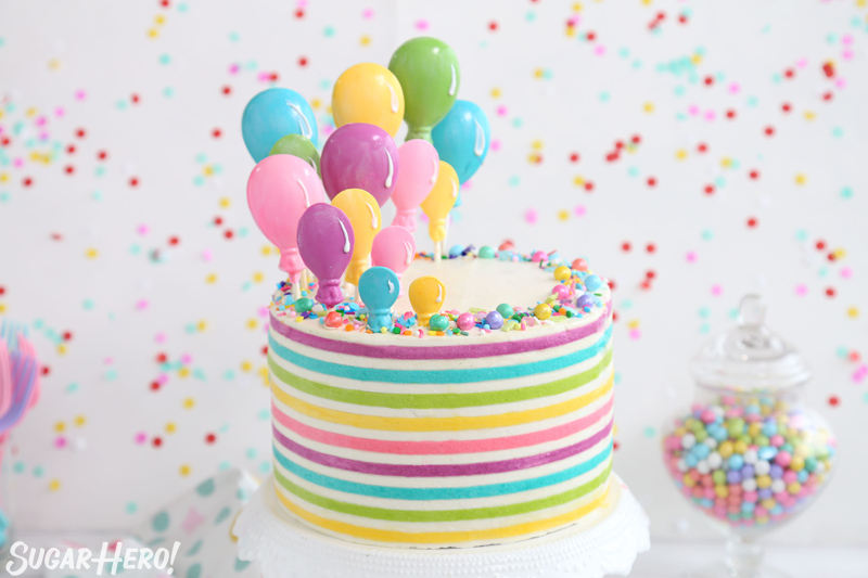 StripedStriped Buttercream Balloon Cake - a round cake with bright, colorful buttercream stripes and candy balloons rising from the top | From SugarHero.com