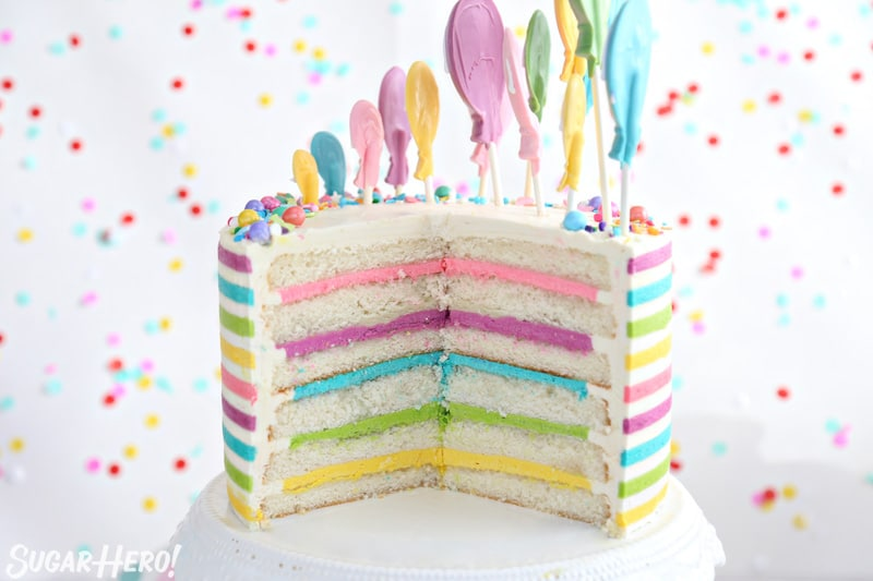 Striped Buttercream Balloon Cake - cake cut open, displaying 6 white cake layers and 5 colorful buttercream layers | From SugarHero.com
