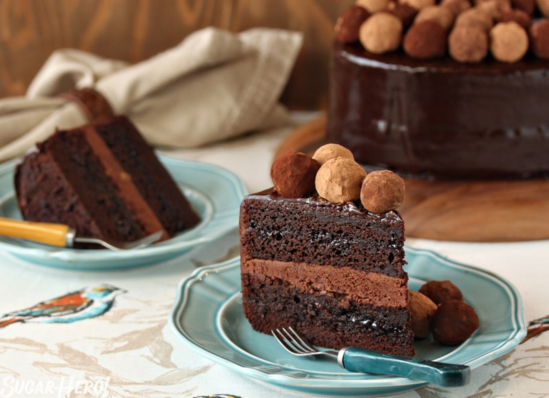 Truffle-Topped Heart Cake - Two slices of chocolate layered cake with chocolate filling showing. | From SugarHero.com