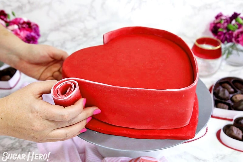 Box of Chocolates Cake - unrolling the red fondant panel along the sides of the cake | From SugarHero.com