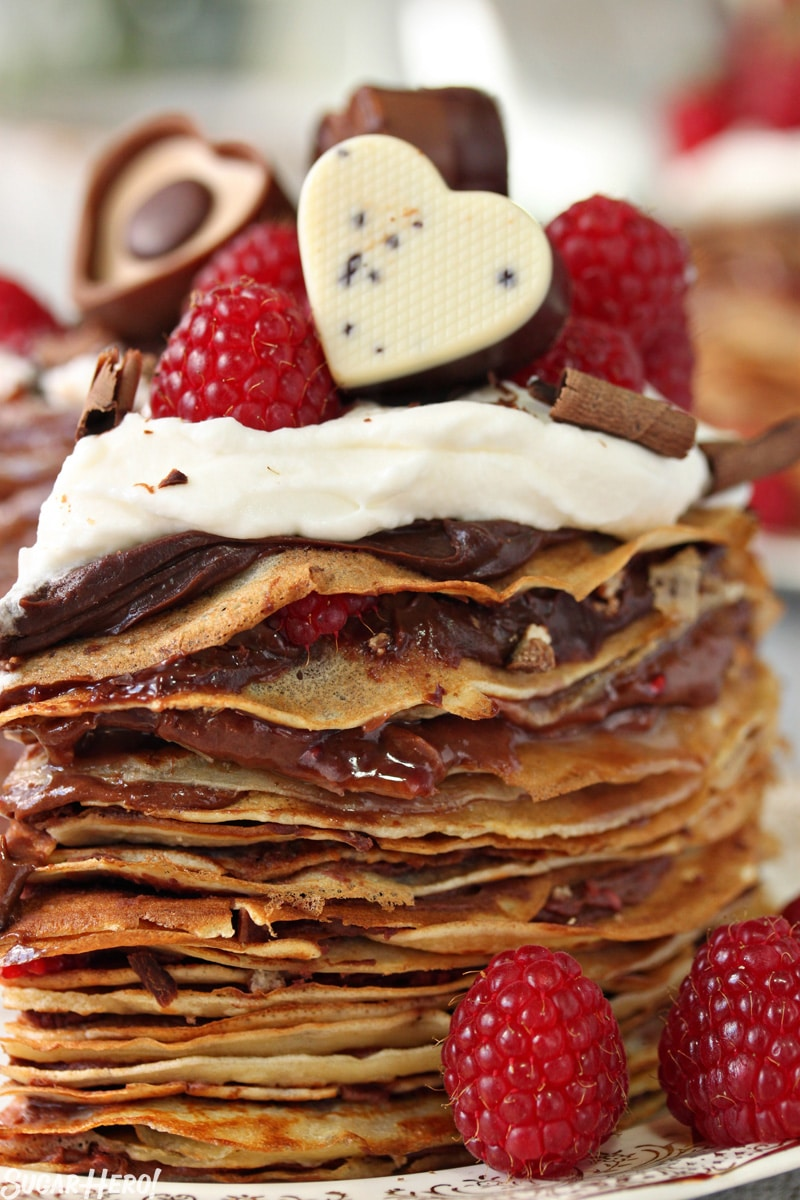 Chocolate Raspberry Mini Crepe Cakes - A close view of the filling and layers of crepes, topped with heart shaped chocolates. | From SugarHero.com