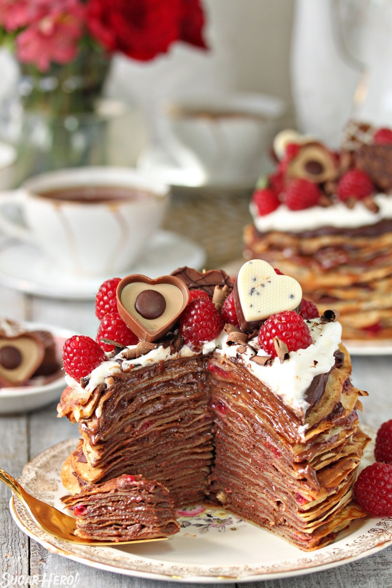 Chocolate Raspberry Mini Crepe Cakes - A single crepe cake with a slice taken out showing the inside of the cake. | From SugarHero.com