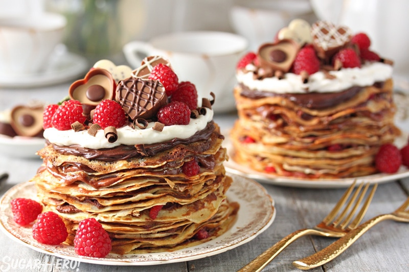 Chocolate Raspberry Mini Crepe Cakes - Two cakes showing the layers of crepes and filling, topped with chocolate and raspberries. | From SugarHero.com