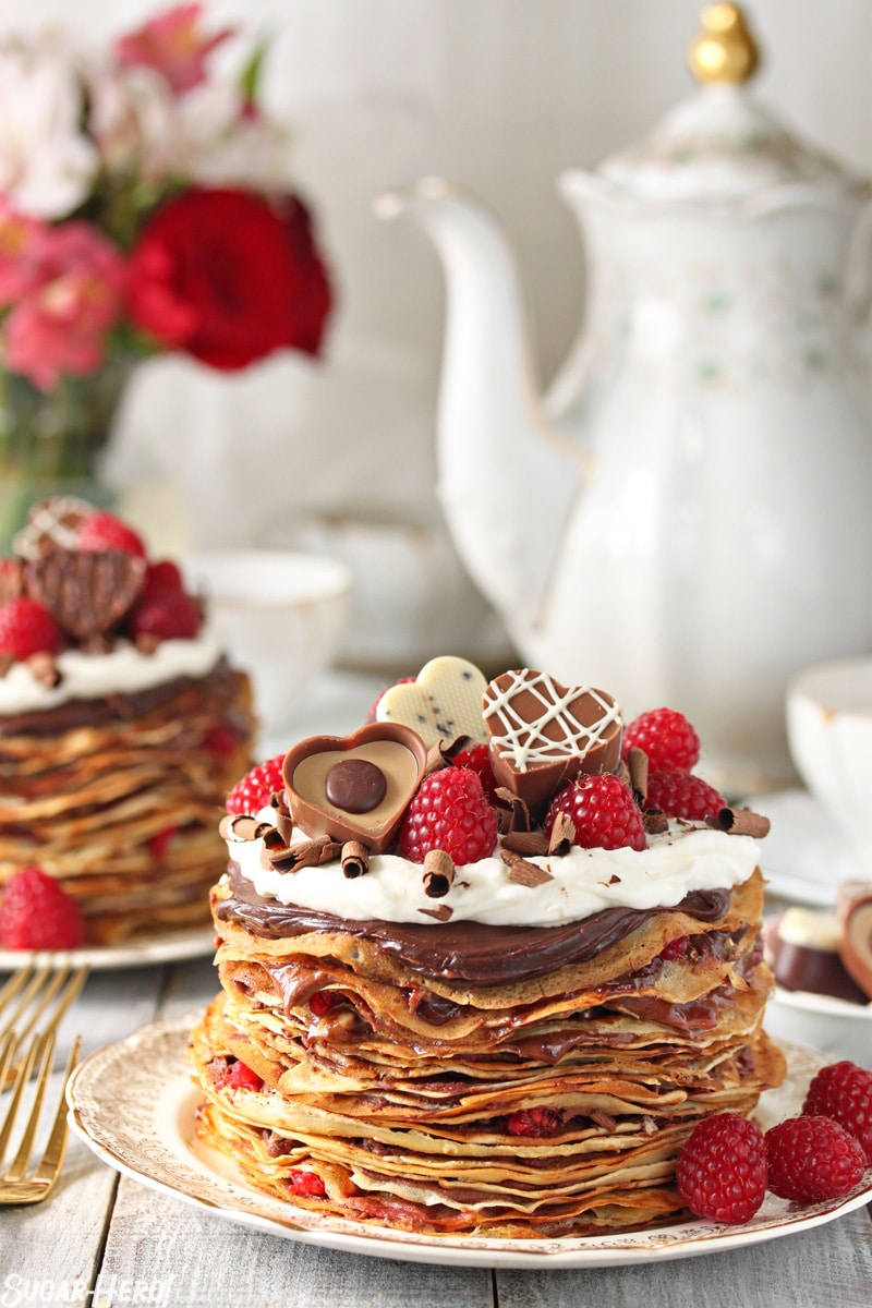 Chocolate Raspberry Mini Crepe Cakes -One crepe cake displayed with chocolates and raspberries on top showing the layers of crepes and filling. | From SugarHero.com