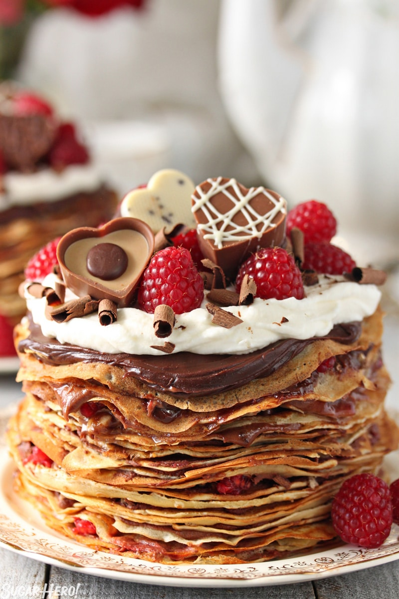 Chocolate Raspberry Mini Crepe Cakes - A single cake with heart shaped chocolates and raspberries on top. | From SugarHero.com