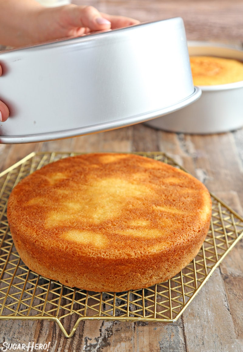 Yellow cake being turned out of a silver cake pan onto a gold cooling rack