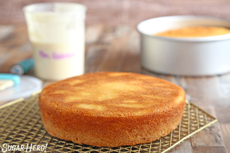Yellow cake cooling on a gold cooling rack with a container of pan release in the background