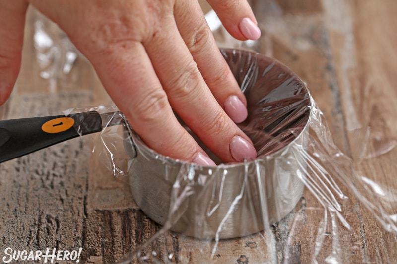 Pressing plastic wrap into the inside of a metal measuring cup