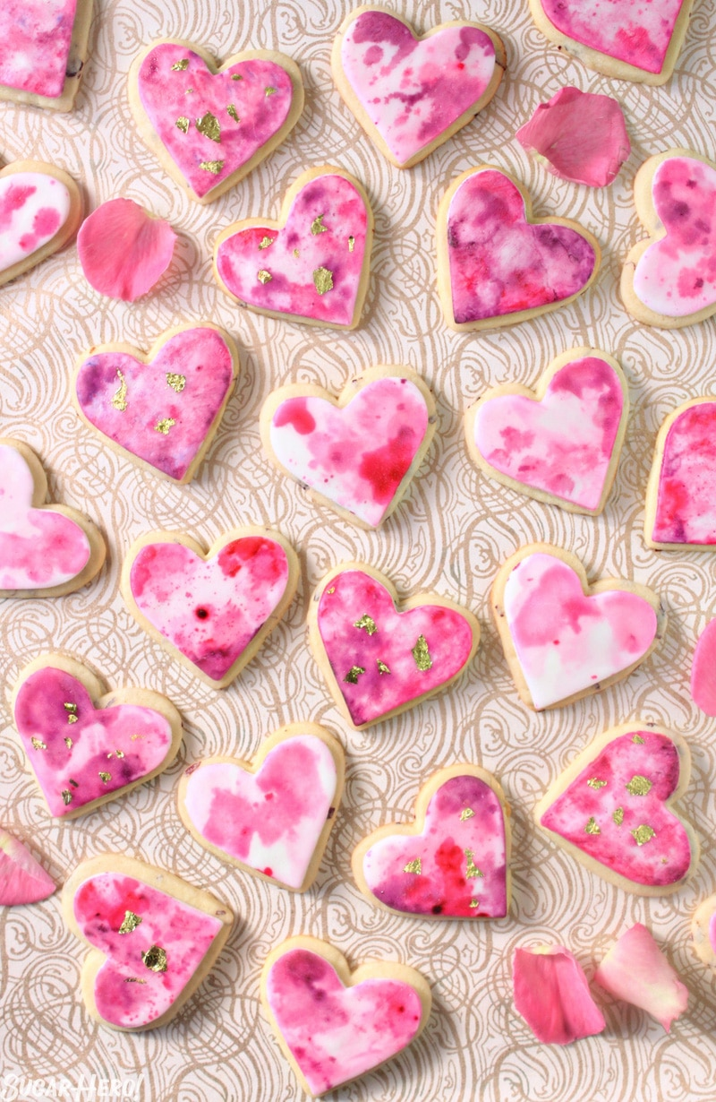Watercolor Rose Sugar Cookies - Multiple cookies displayed with rose petals throughout. | From SugarHero.com