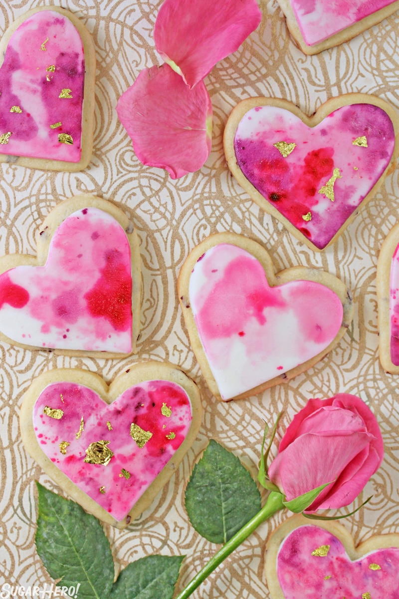 Watercolor Rose Sugar Cookies - Multiple cookies displayed with the a pink rose, showing the pink and purple watermarks on the cookies. | From SugarHero.com