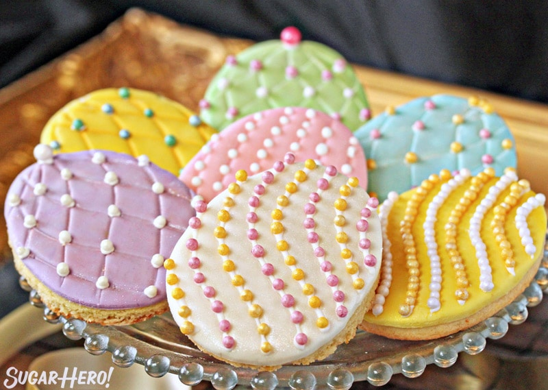 Easter egg sugar cookies on a gold tray with colorful sugar pearls