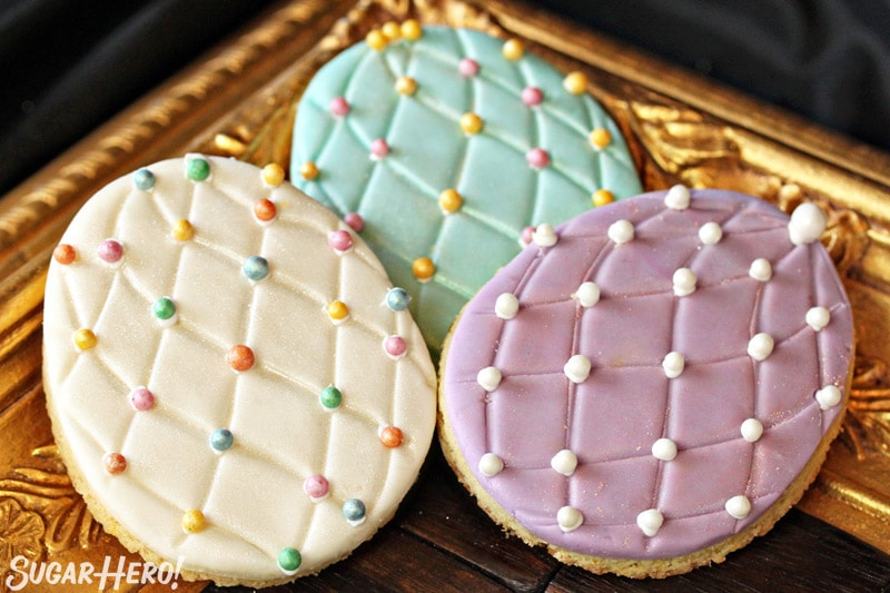 Three Easter egg sugar cookies on a gold tray