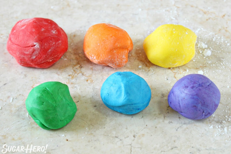 Six balls of fondant in rainbow colors on a marble countertop