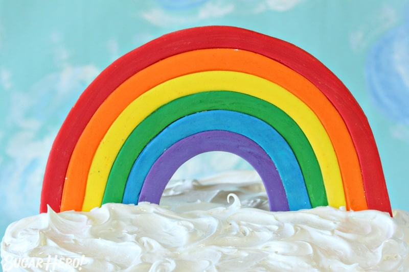 Fondant Rainbow Cake Topper on top of a cake with fluffy white frosting
