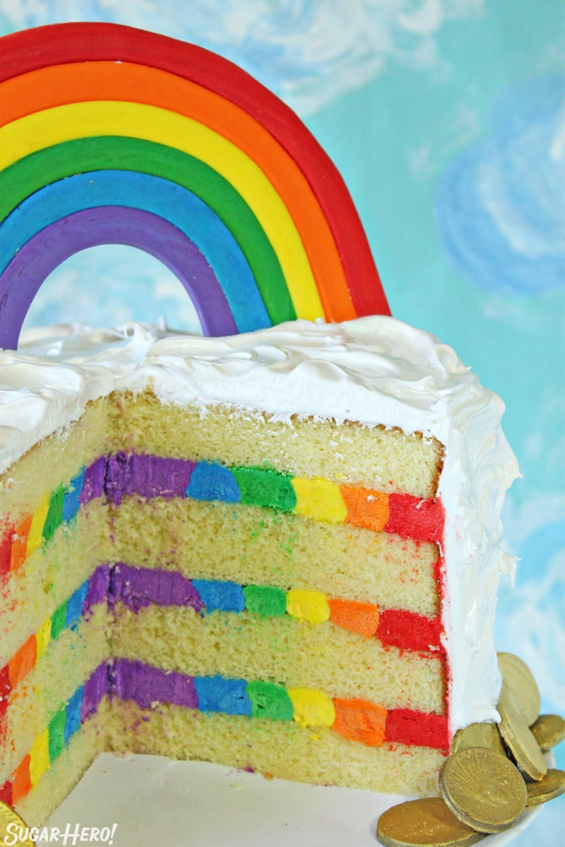 Rainbow cake cut open with rainbow frosting inside