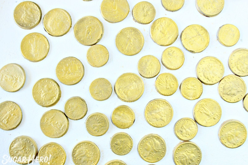 Edible chocolate gold coins on white surface