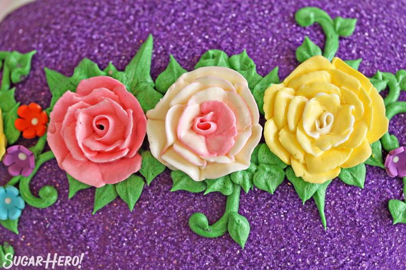 Three buttercream roses on a background of green leaves and purple sparkling sugar