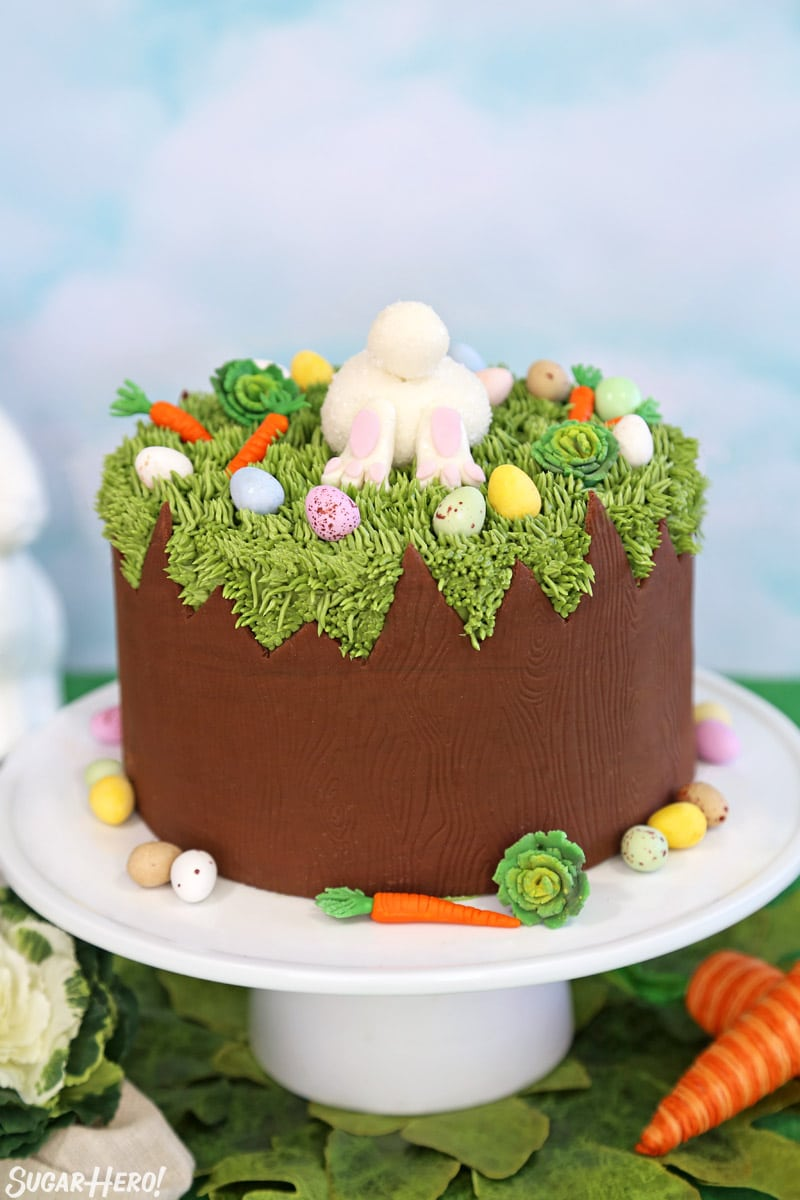 Chocolate Easter Bunny Cake on a white cake stand with fondant decorations and chocolate eggs around the base