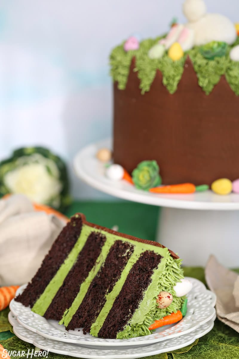 A slice of Chocolate Easter Bunny Cake on a white plate, with the whole cake in the background on a white cake stand