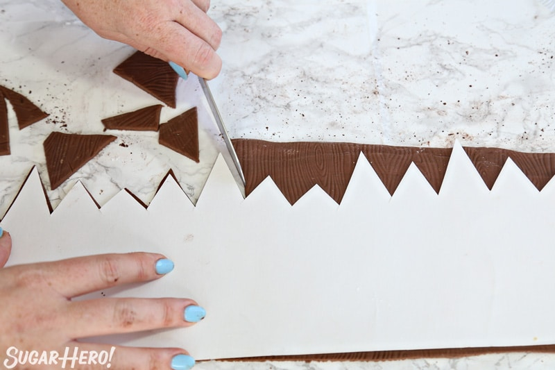 Cutting the top of the brown fondant strip to look like a jagged fence