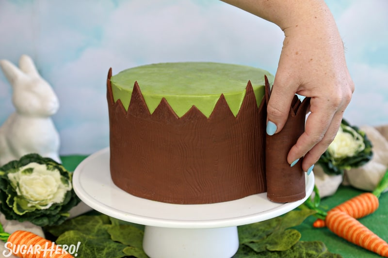 Rolling the brown fondant fence around the base of the green bunny cake