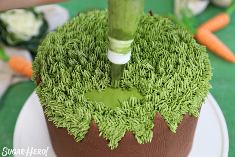 Piping green buttercream onto the top of the cake with a grass piping tip