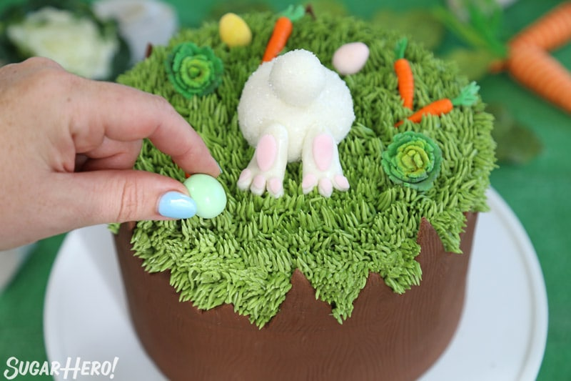 Placing a chocolate egg on top of the Chocolate Easter Bunny Cake