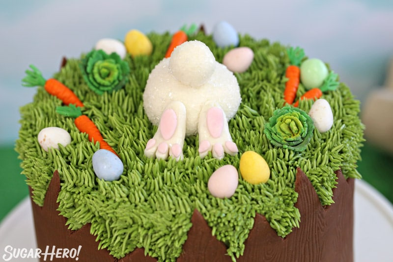 Close-up of the top of the Chocolate Easter Bunny Cake, with a fondant bunny butt and fondant carrots and cabbages