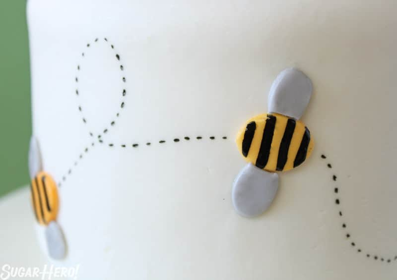 Bumblebee Cake - A close up shot of a bee made of fondant with a black trail. | From SugarHero.com