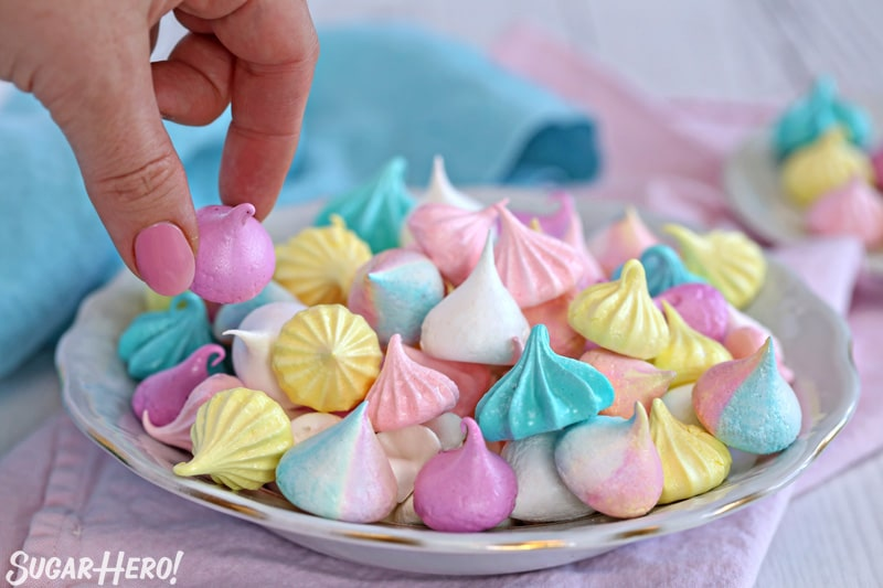 Hand picking up purple meringue kiss from plate of assorted meringues