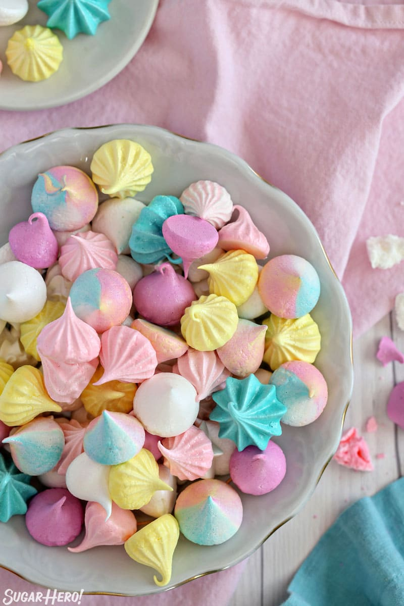 Overhead shot of colorful meringue cookies piled together in a large bowl
